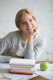 Portrait of a young smiling girl with books and apple. Portrait of a young smiling student girl sitting at the desk with books and green apple, propping up chin Stock Photos
