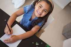 Portrait of a young smiling girl drawing on table Royalty Free Stock Photo