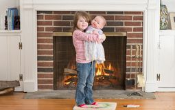 Portrait of a young smiling girl hold a baby doll in front of a fireplace dressed for valentine`s day Stock Image
