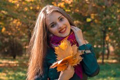 Portrait of a young smiling girl with long straight hair that keeps dry leaves in hand Royalty Free Stock Image