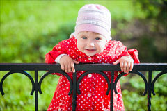 Portrait of a young smiling girl in a red coat with polka dots.  stock image
