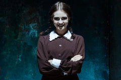 Portrait of a young smiling girl in school uniform as killer woman Royalty Free Stock Photo
