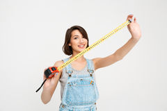 Portrait of young smiling girl, showing tape measure Stock Images