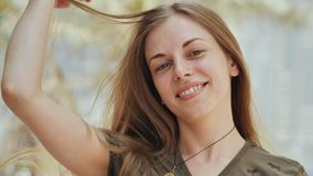 Portrait of a young and smiling girl in summer day. Face close-up. Posing with hair. stock footage