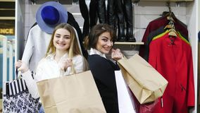 Portrait of young smiling girls showing their shopping bags. Two beautiful young girls with packages in their hands are happy shopping in the store. Portrait of stock video footage
