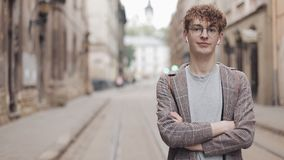 Portrait of Young Smiling Hipster Guy in Glasses and Earphones Standing with Crossed Hands at Old City Street Background stock footage