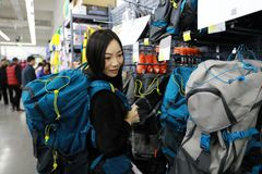 Choosing new knapsack shanghai decathlon shop. Portrait of young smiling lady in the outdoor department looking at fashionable knapsack sale Royalty Free Stock Photography