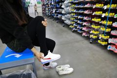Trying new shoes at shanghai decathlon shop. Portrait of young smiling lady in the shoes department Trying new shoes during sale Royalty Free Stock Photo