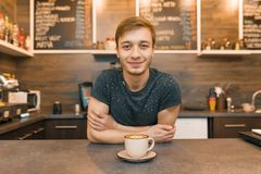 Portrait of young smiling male cafe worker, standing at the counter. Man with folded hands with freshly made coffee royalty free stock image
