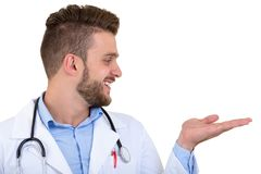 Portrait of a Young smiling male doctor pointing finger away isolated on a white background.  Stock Photos