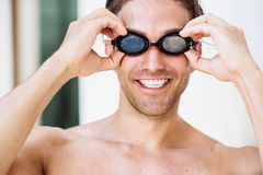Portrait of  young smiling male swimmer in googles. Young handsome  sportsman in googles getting ready for a swim Royalty Free Stock Photo