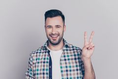 Portrait of young, smiling man in checkered shirt with stubble,. Bristle gesturing v-sign over grey background Royalty Free Stock Photos