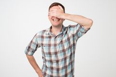 Portrait of a young smiling man covering his eyes with his hand stock images