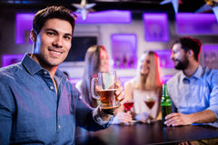 Portrait of young smiling man having glass of beer at bar counter. Portrait of young smiling men having glass of beer at beer counter in bar Stock Image