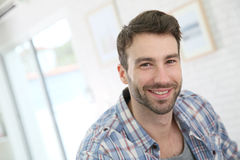 Portrait of a young smiling man indoors stock photo