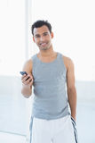 Portrait of a young smiling man with mobile phone. Against bright background Royalty Free Stock Image