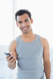 Portrait of a young smiling man with mobile phone. Against bright background Royalty Free Stock Photos