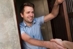Portrait of young smiling man opening the door to his friend and welcoming him shaking hand. Invite somebody for party Stock Image