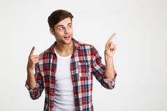 Portrait of a young smiling man pointing. Two fingers away at copy space isolated over white background Stock Images