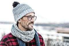Portrait of young smiling man profile in glasses and warm knitted clothes for city man. Portrait of young smiling man profile in glasses. Winter warm knitted Stock Photography