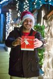 Portrait of young smiling man in Santa hat holding present next. To Christmas decoration Stock Photography