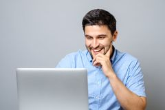 Portrait of young smiling man sitting at the desk with laptop. Computer over gray background Royalty Free Stock Photos