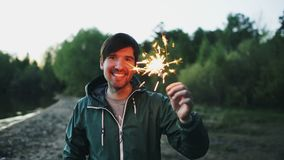 Portrait of young smiling man with sparkler celebrating at beach party. Portrait of young smiling man with sparkler celebrating at the beach party Royalty Free Stock Image