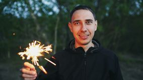 Portrait of young smiling man with sparkler celebrating at beach party. Portrait of young smiling man with sparkler celebrating at the beach party Royalty Free Stock Photo