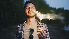Portrait of young smiling man with sparkler celebrating at beach party. Portrait of young smiling man with sparkler celebrating at the beach party Stock Image