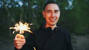 Portrait of young smiling man with sparkler celebrating at beach party. Portrait of young smiling man with sparkler celebrating at the beach party Stock Images