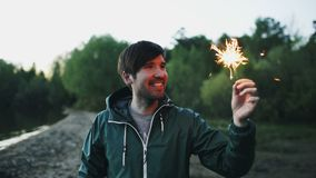 Portrait of young smiling man with sparkler celebrating at beach party. Portrait of young smiling man with sparkler celebrating at the beach party Stock Photos