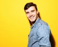 Portrait of young smiling man standing against yellow background. Portrait of a smart young smiling man standing against yellow background Royalty Free Stock Image