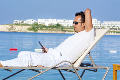 Portrait of young smiling man with  tablet in the hand on a sea beach Stock Photos