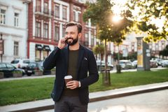 Portrait of a young smiling man. Talking on mobile phone while holding coffee cup and walking on a city street Royalty Free Stock Photo
