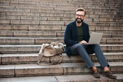 Portrait of young smiling man using laptop computer. While sitting on stairs outdoors Royalty Free Stock Image