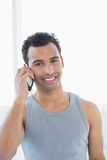 Portrait of a young smiling man using mobile phone. Against bright background Stock Images