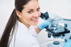 Portrait of young smiling medical researcher looking through mic. Young woman medical researcher looking through microscope in laboratory, medicine concept Stock Images