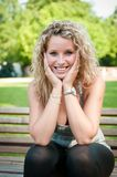 Portrait of young smiling person. Exterior portrait of young smiling woman sitting on bench in park Royalty Free Stock Photo