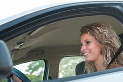 Portrait of young smiling person driving car. Young beautiful smiling woman driving car - portrait through side window Royalty Free Stock Photography