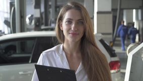 Portrait of young smiling pretty woman manager or client with contract on the background of car service stock footage