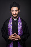 Portrait: young smiling priest. Studio portrait on black background Stock Photography