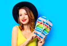 Woman with summer flip-flops. Portrait of young smiling red-haired white european woman in hat with summer flip-flops on blue background stock photography