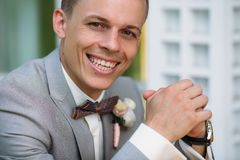 Portrait of a young smiling stylish man in a classic business suit in gray with a white shirt and a bow tie. A young guy. Is a businessman is sitting at a table Stock Image