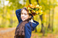Portrait of young smiling teenage girl holding autumn leaves bouquet. Fall season. Stock Photography