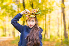 Portrait of young smiling teenage girl holding autumn leaves bouquet. Fall season. Stock Images