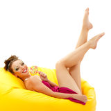 Portrait of young smiling woman with beautiful make-up holding s. Weet candy lying on yellow sofa isolated on white background Royalty Free Stock Image