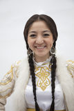 Portrait of young smiling woman with braids in traditional clothing from Kazakhstan, studio shot Stock Photos