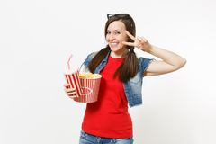 Portrait of young smiling woman in 3d glasses watching movie film, holding bucket of popcorn and plastic cup of soda or. Cola showing victory sign isolated on stock photo