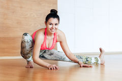 Portrait of a young smiling woman doing stretching before practicing yoga Royalty Free Stock Photography