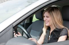 Portrait of young smiling woman driving car Stock Image